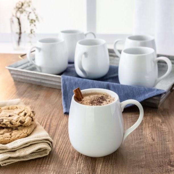 One white mug filled with beverage and a cinnamon stick, next to cookies placed on top of a dish towel, and tray with rest of the mug set in the background.