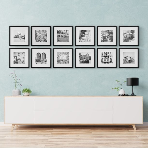 12 piece frame set with black and white photos hanging above a white console.