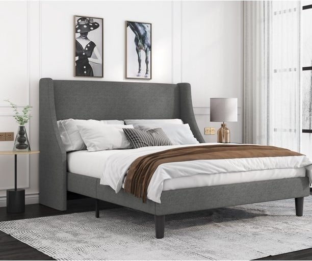 Gray upholstered bed in a bedroom with a rug underneath, artwork above and nightstands on either side.