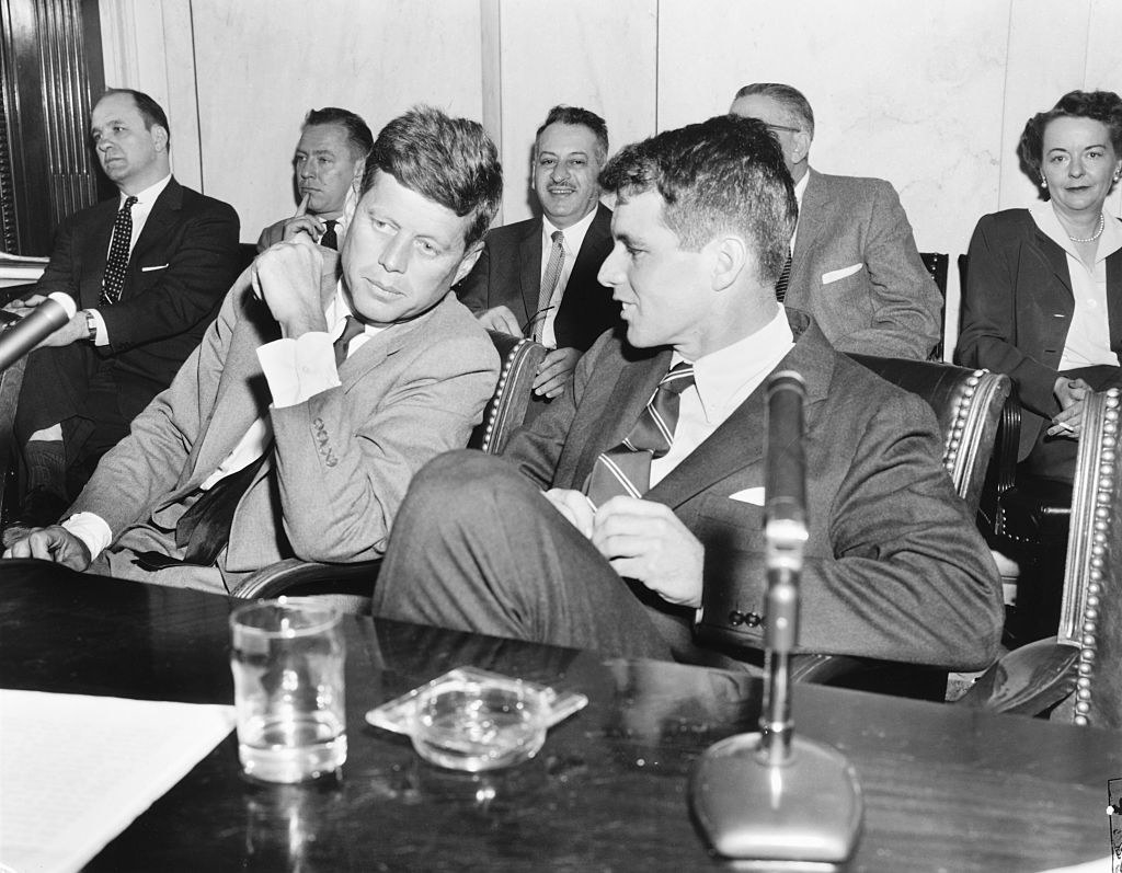 JFK and Robert Kennedy discuss something at a hearing