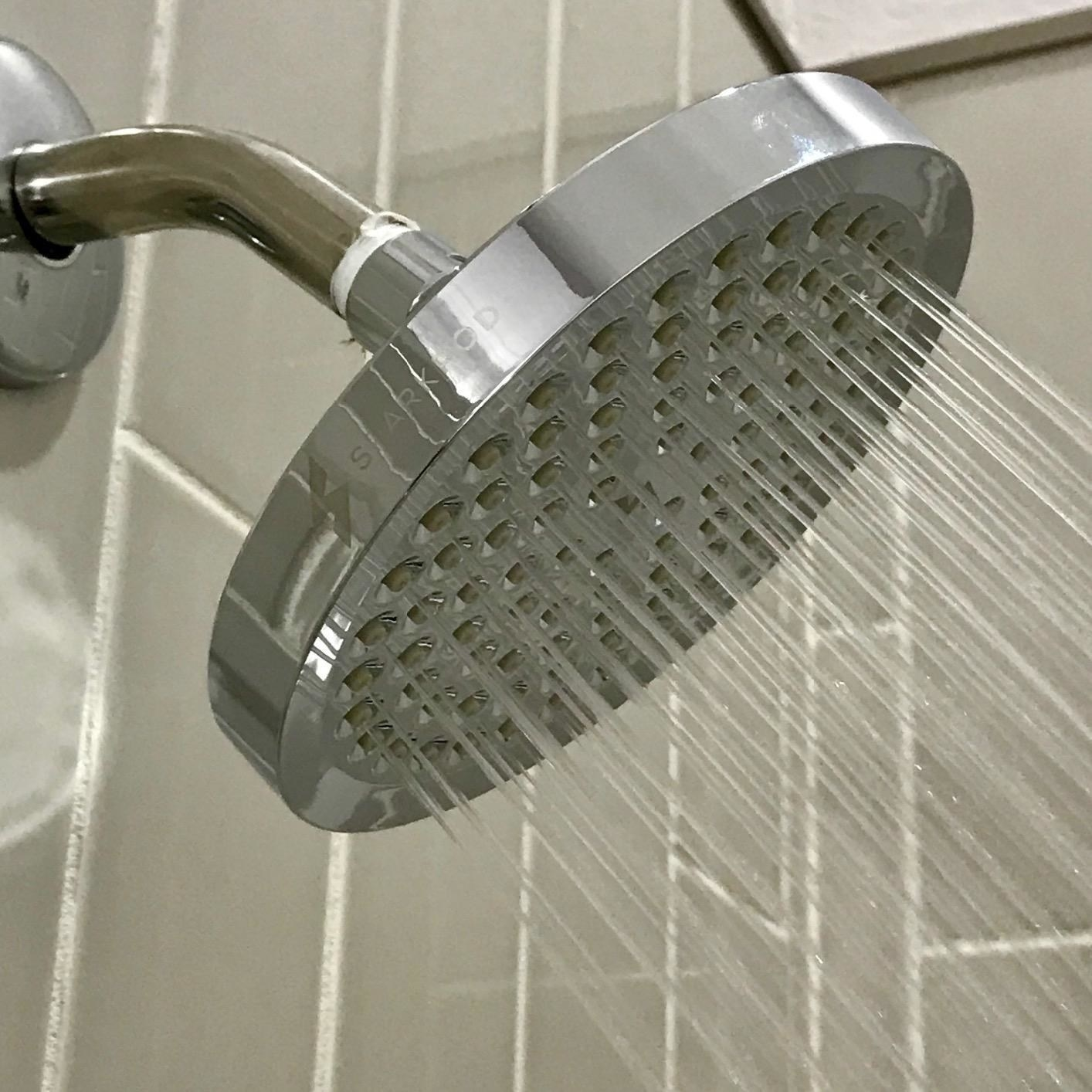reviewer photo of the shower head with water spraying out of it