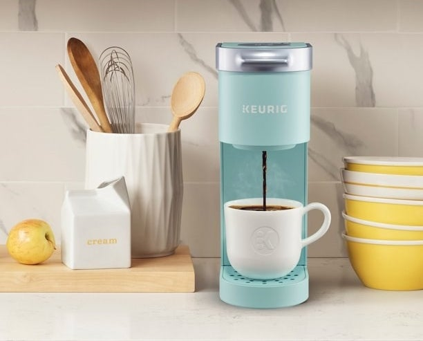 Coffee maker shown in a blue color, with white cup, sitting on a kitchen countertop surrounded by kitchen items.