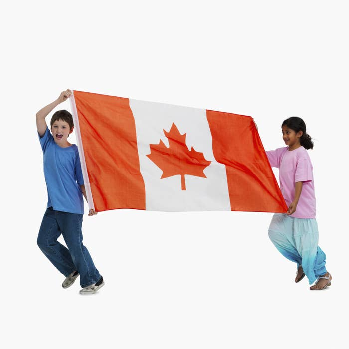 Two children holding up a large Canadian flag