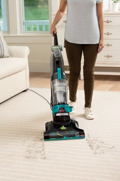 A model vacuuming a striped rug with dirt on it with the vacuum cleaner.