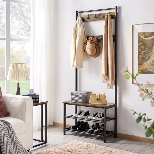 Coat rack shown with jacket, hat and scarf hanging on it, shoes stored on shelves and a bag and storage box on the bench.