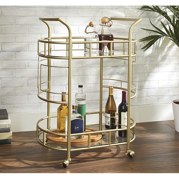 Gold bar cart with two glass shelves, holding a wood tray and various bottles.