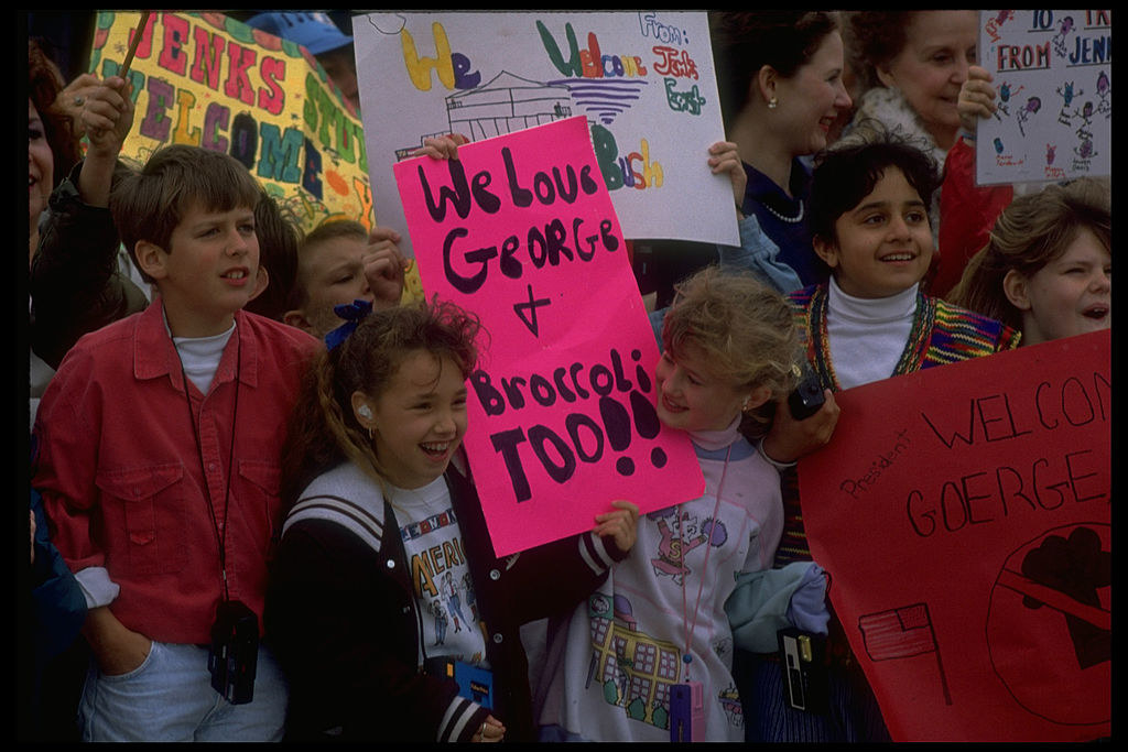 """some kids hold a sign that says """"we love George and broccoli too!"""""""