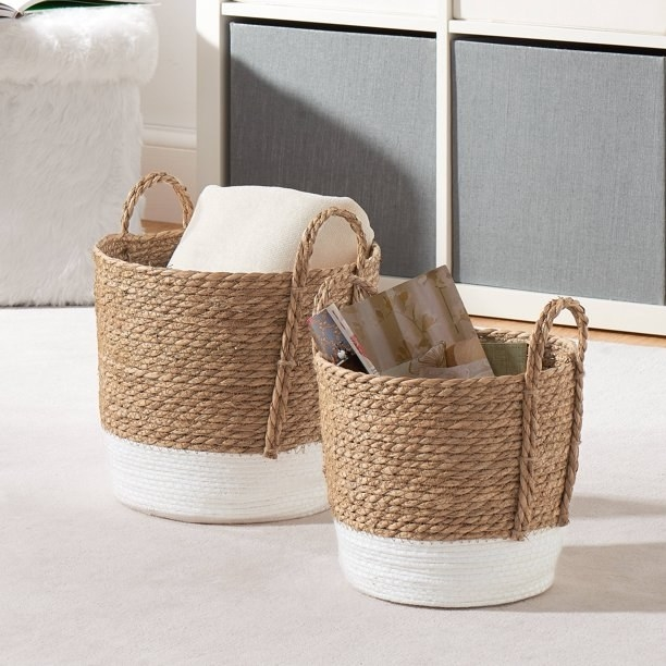 Two different sized seagrass baskets with handles holding various items, sitting on the floor.