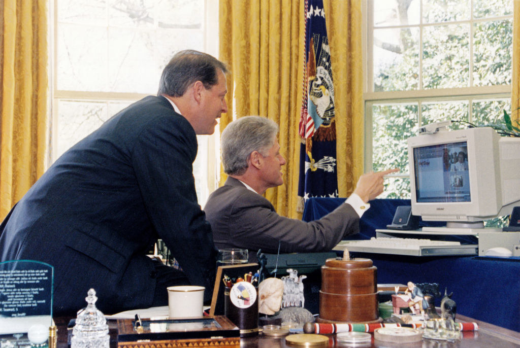 Bill Clinton looking at a computer in the oval office