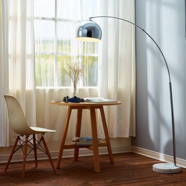 """Floor lamp shown in """"Chrome"""" finish in a room next to a small table and chair."""