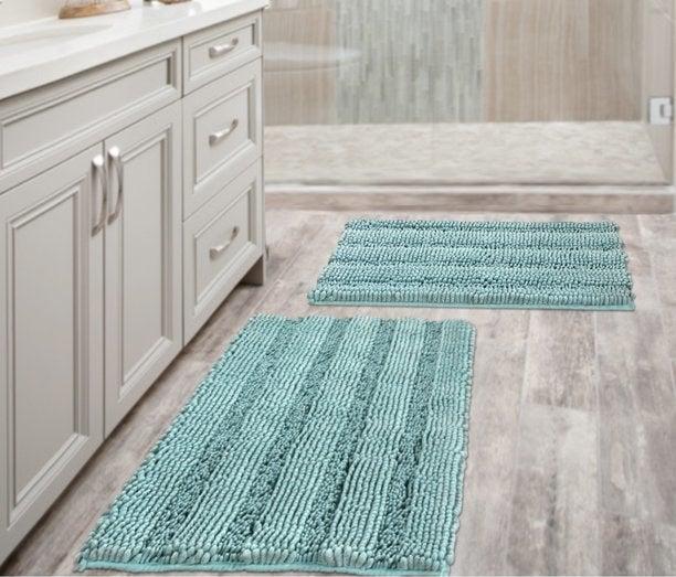 Two aqua blue mats in a bathroom.