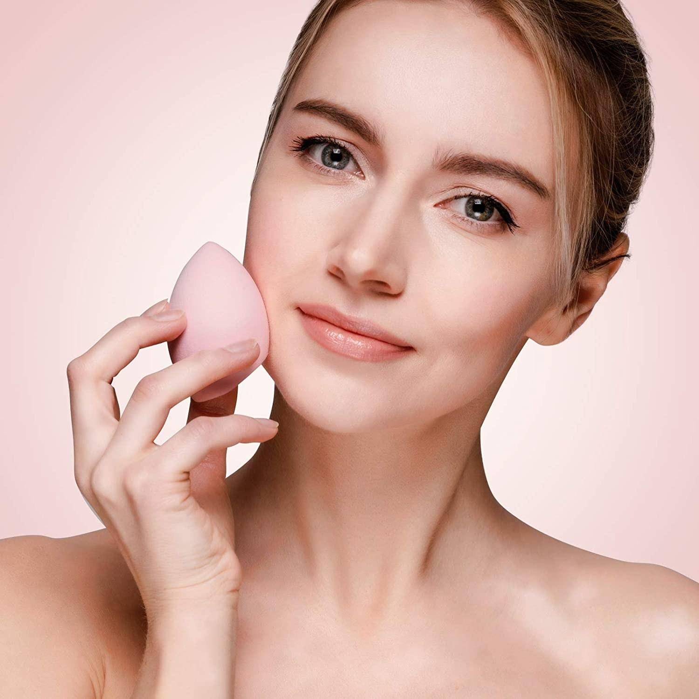 Persona utilizando esponja aplicadora de maquillaje