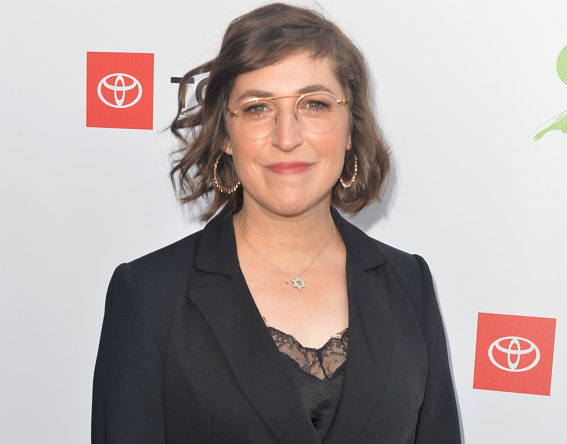 Mayim wears glasses and a suit jacket at an event