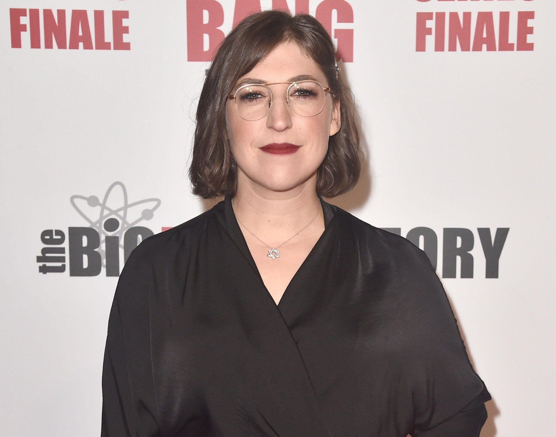 Mayim wears a black wrap top at an event