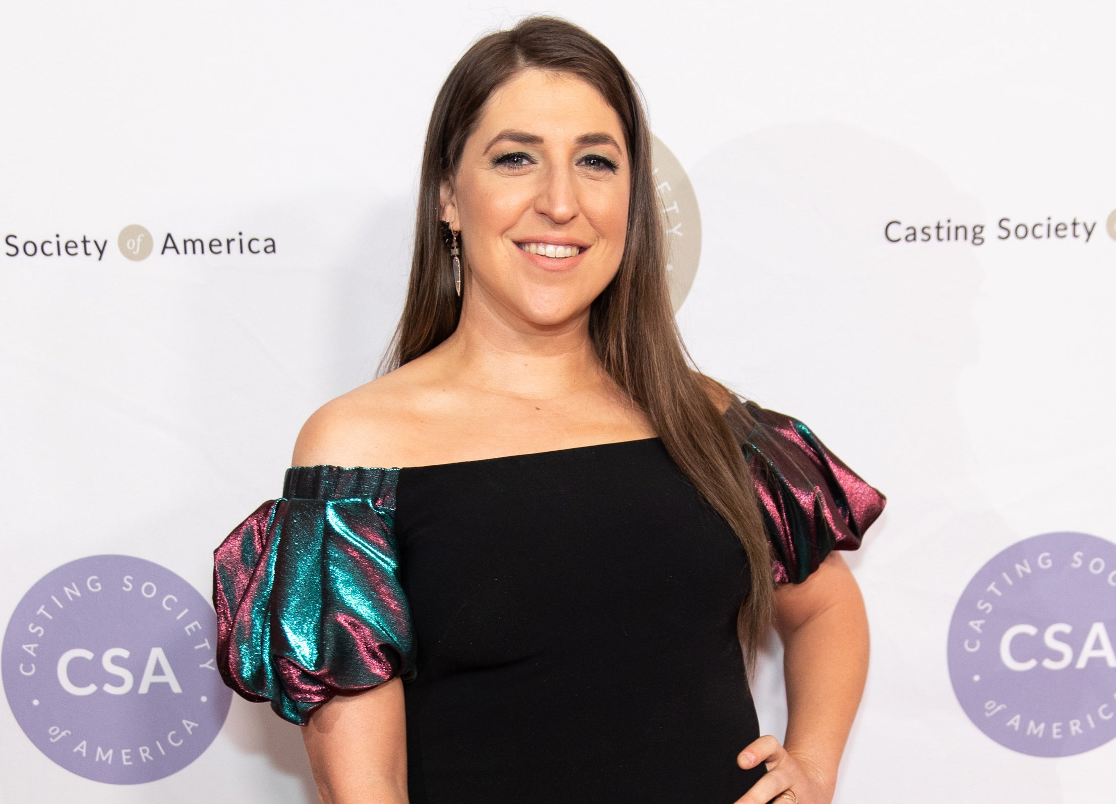 Mayim smiles while wearing an off the shoulder dress at an event