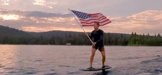 In this still, Mark Zuckerberg is riding a hydrofoil on the water and holding an American flag