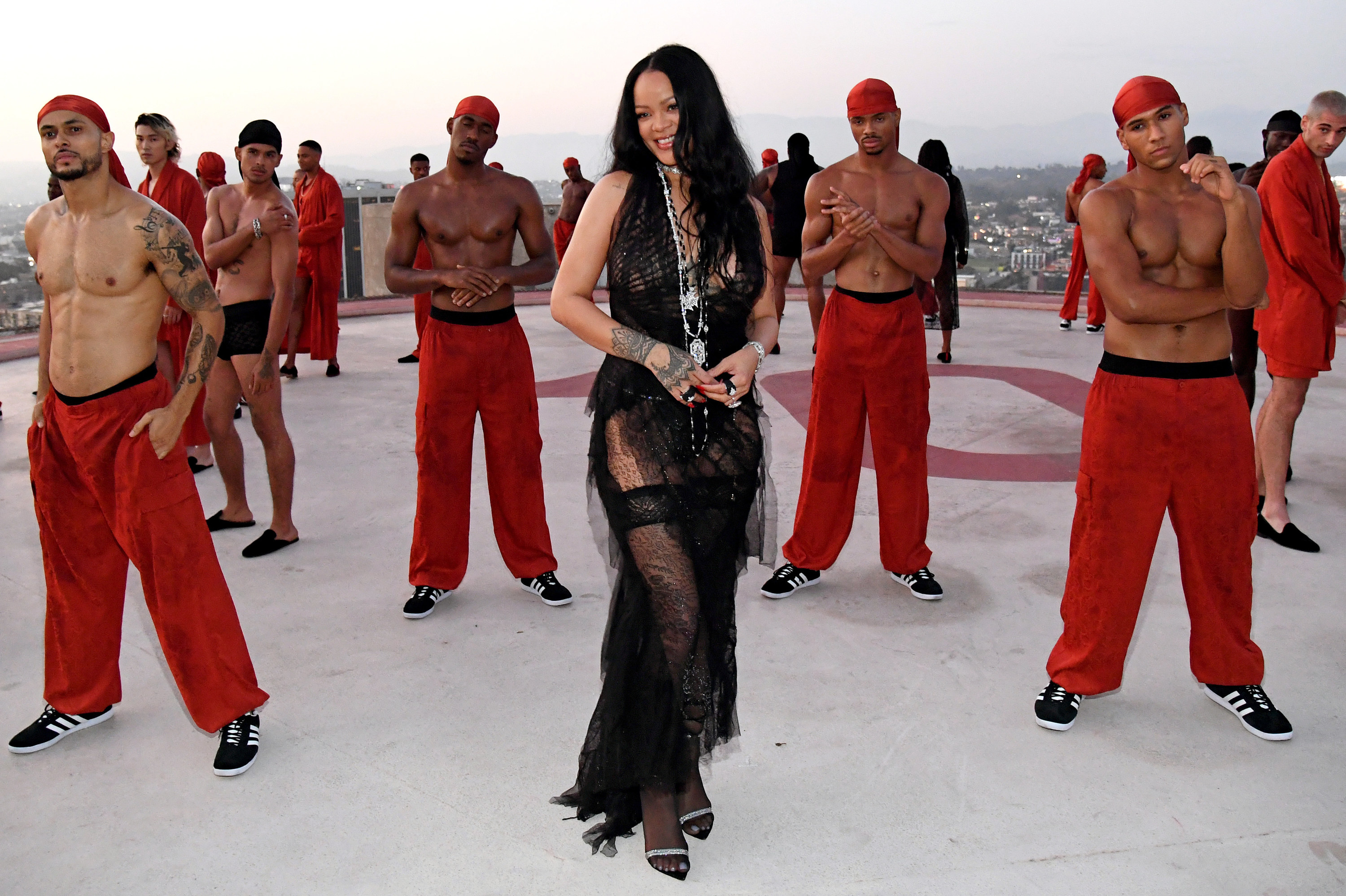 Rihanna standing in the middle of a group of shirtless people wearing matching durags and pants