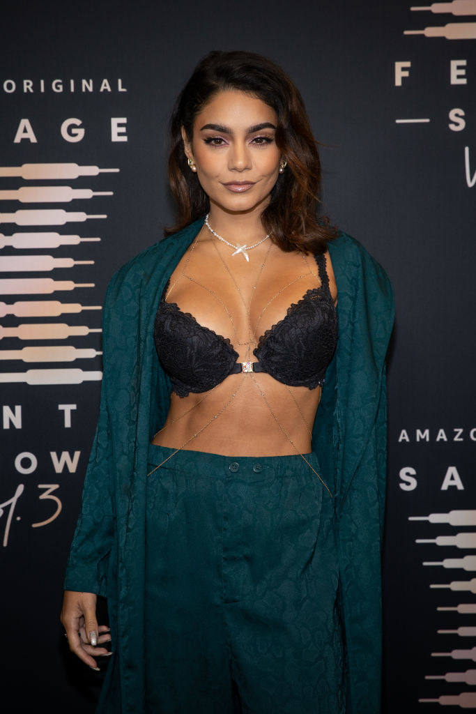 Vanessa poses on the red carpet in a dark bra and pajama set with the shirt completely open