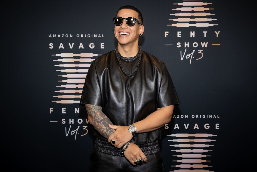 Daddy Yankee smiles on the red carpet while wearing a leather-like shirt with satin pants