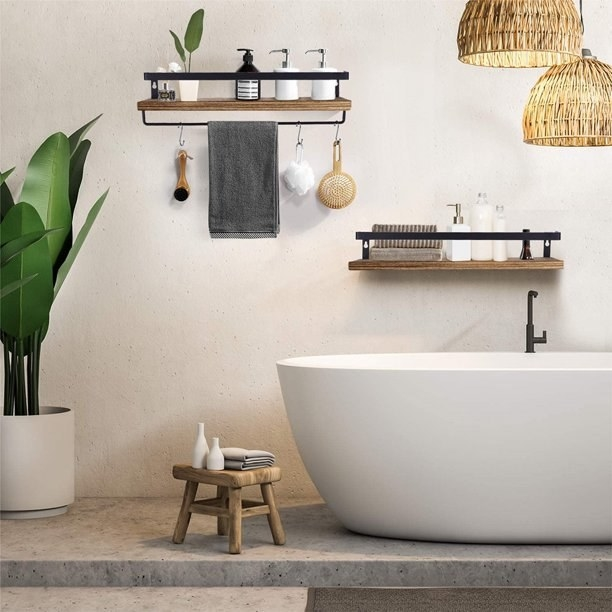 Floating shelves (one with a towel bar, one without) shown on a bathroom wall.