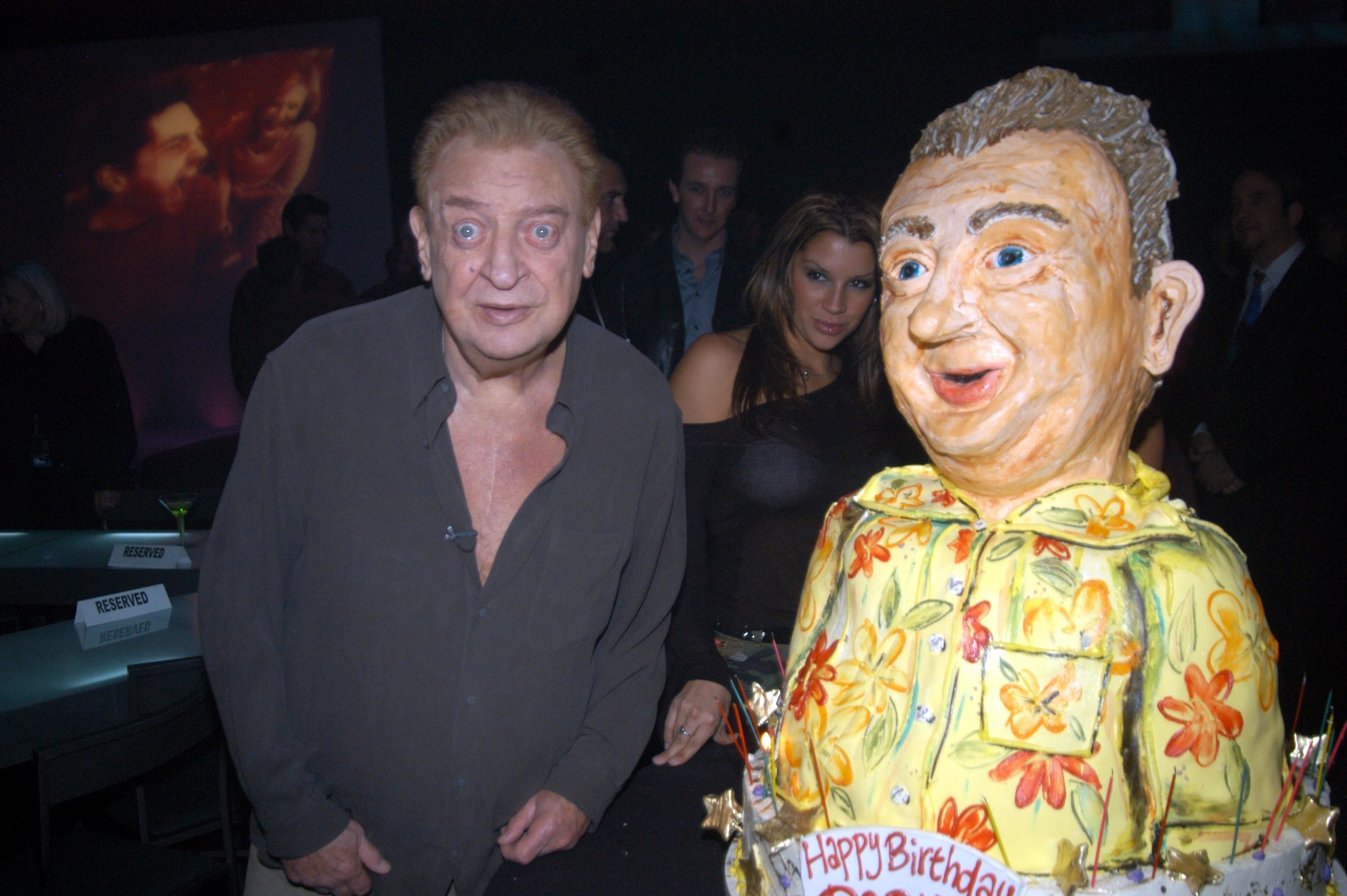 Rodney Dangerfield next to a cake with a model of himself in a Hawaiian shirt