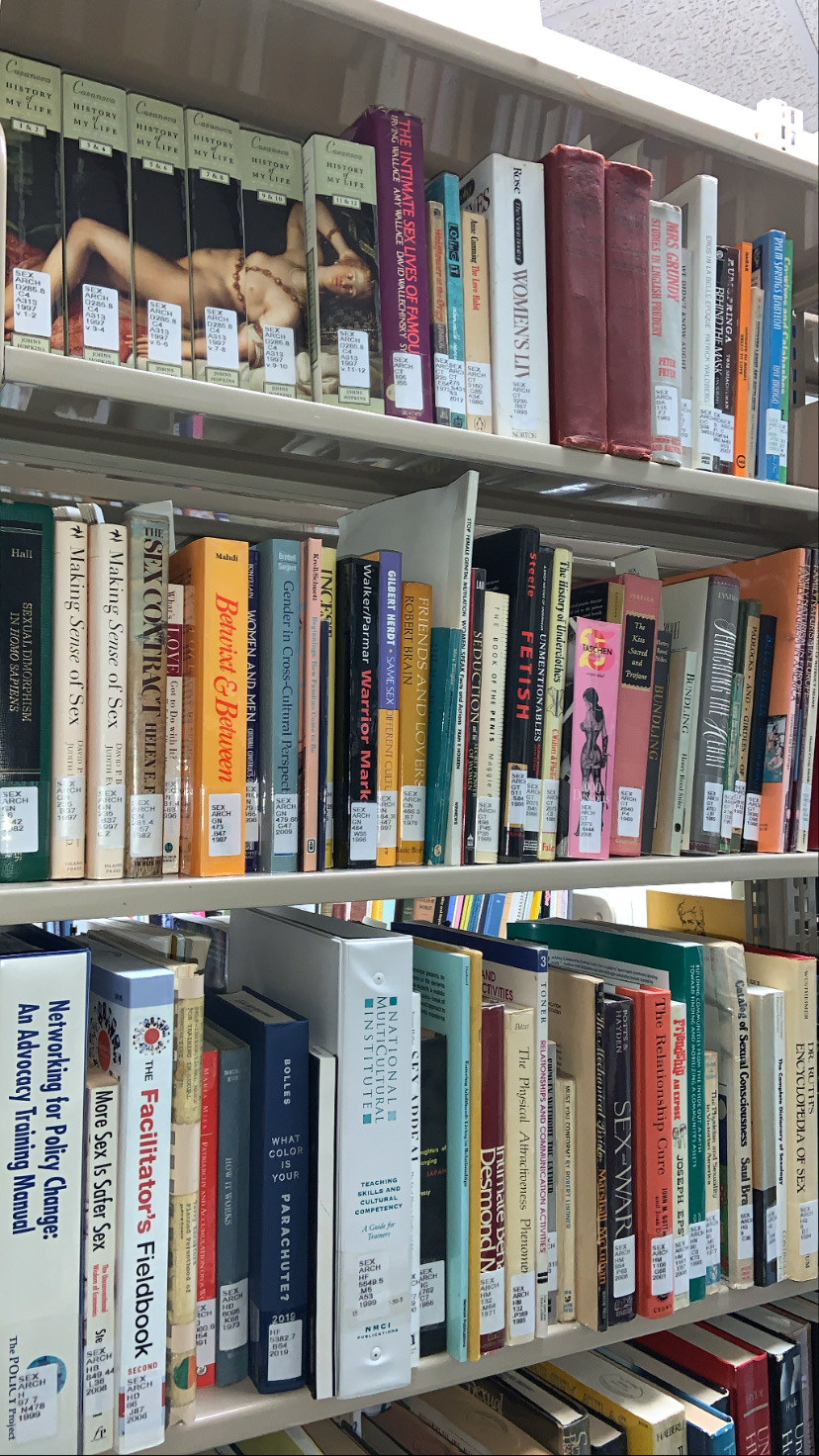 Human sexuality books on shelves inside of a library