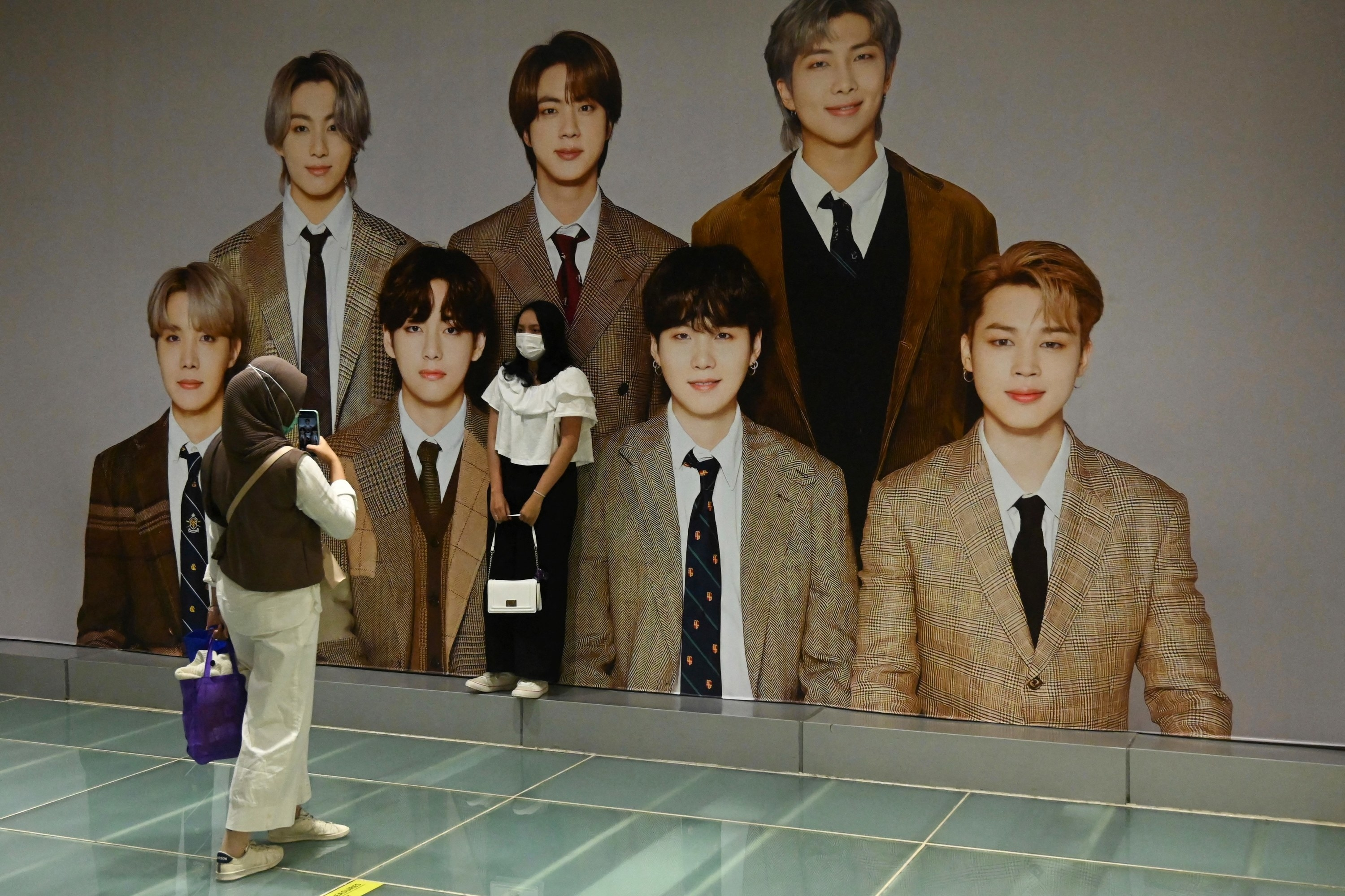 A person taking a photo of someone else as they pose next to a mural of BTS