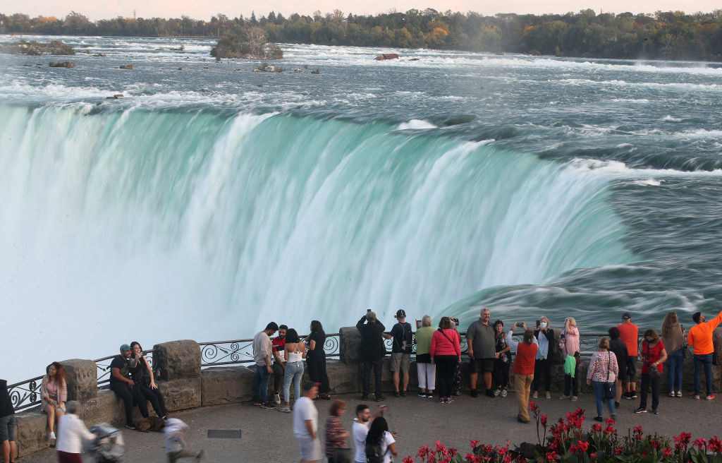 People looking and photographing the view of Niagara Falls.