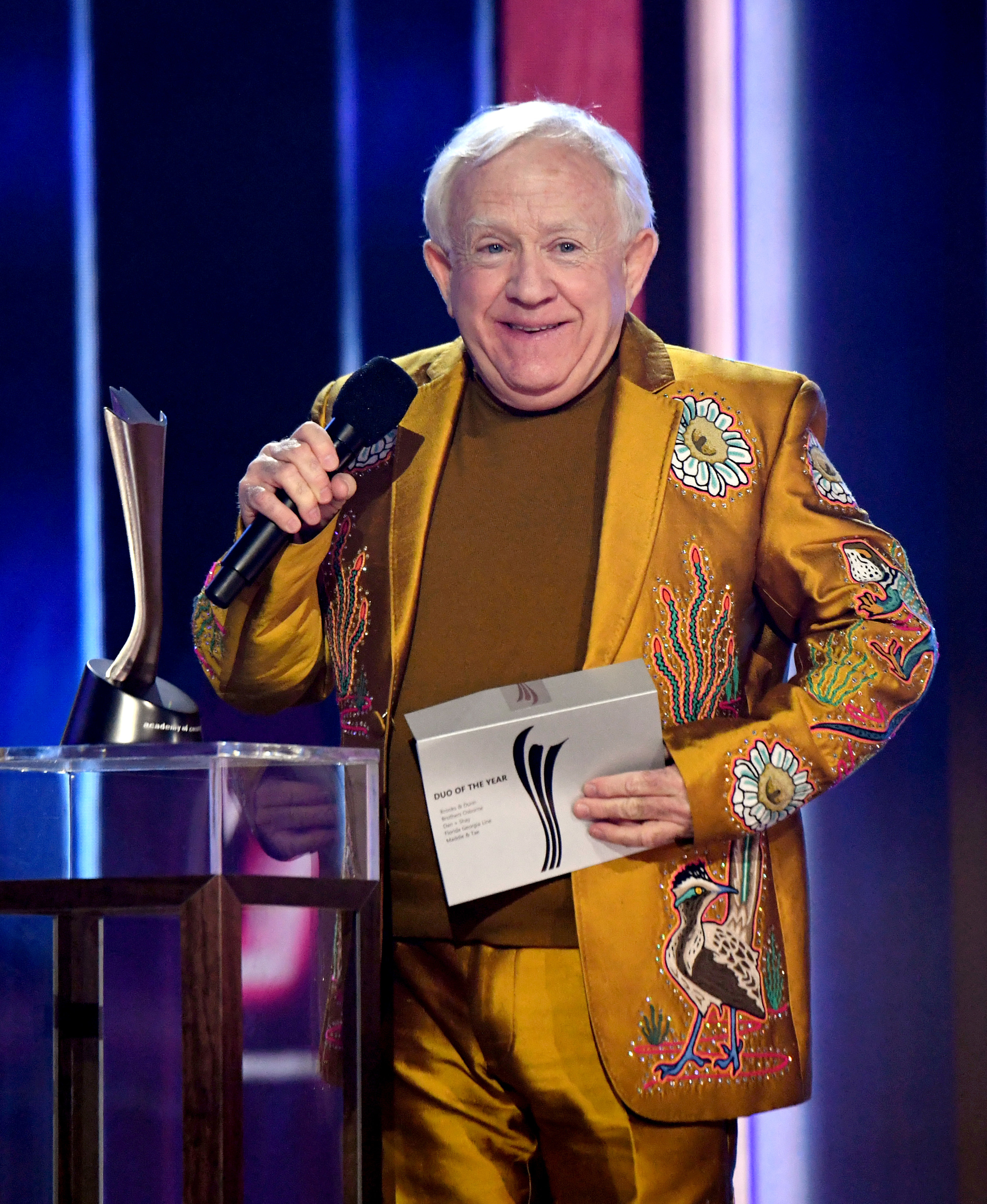 Leslie in a shiny embroidered suit with matching shirt while presenting an award