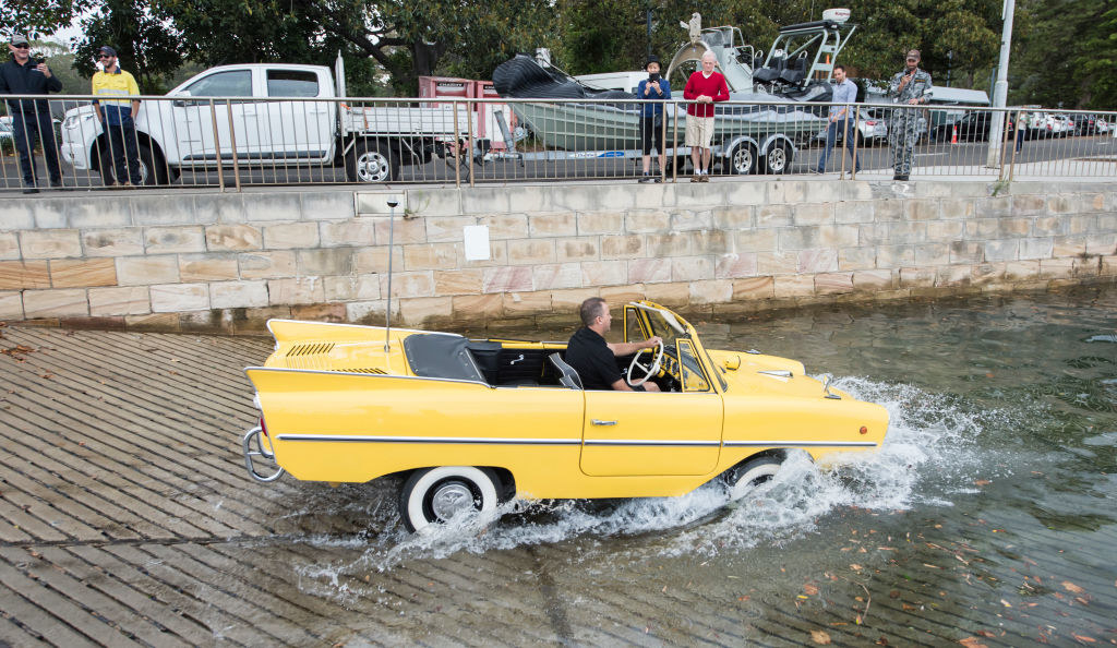 Someone demonstrating an amphicar driving into the water