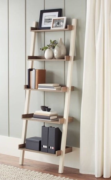 Leaning bookcase shown filled with books, picture frames and accessories.