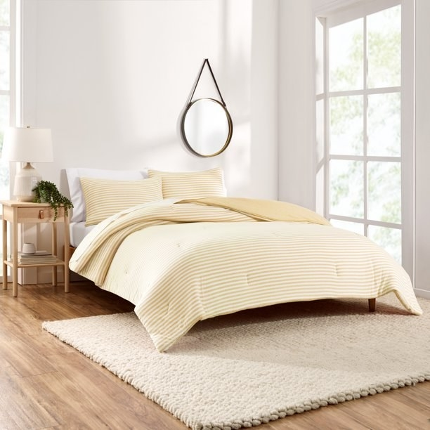 """Bed made with comforter set in color """"Yellow""""."""