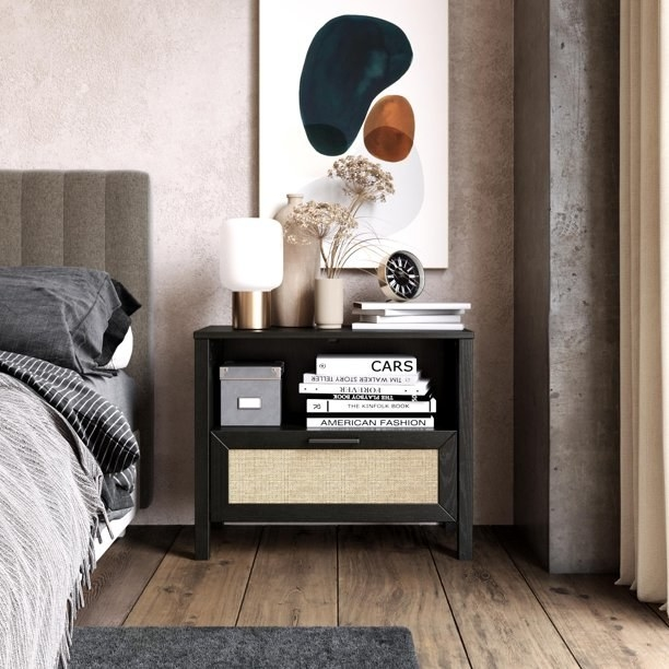 Nightstand shown in a bedroom, filled with books and topped with vases, a lamp, more books and a clock.