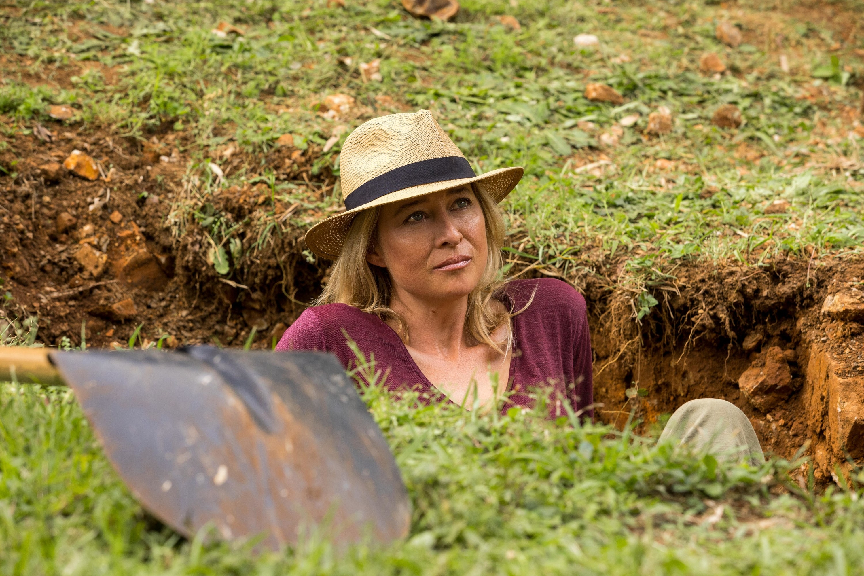 A woman sitting in a grave she dug