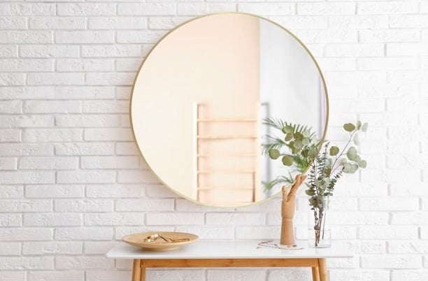 """Mirror in color """"Gold"""" hanging above a console on a white brick wall."""