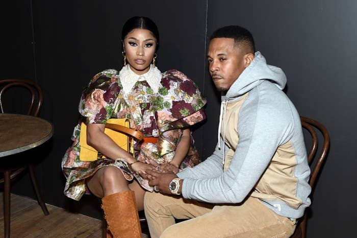 Nicki and Kenneth holding hands as they sit at a table