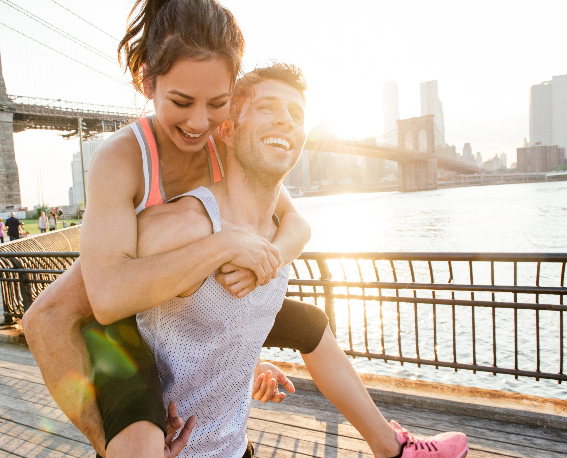 A guy giving his girlfriend a piggyback ride as they exercise
