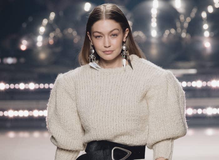 Gigi wears a sweater while walking a runway