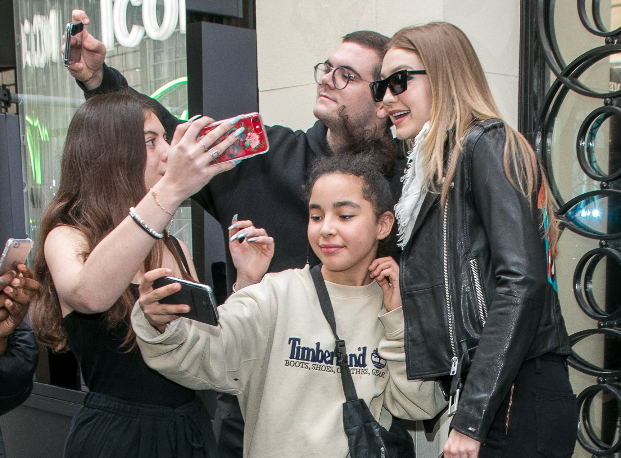 Gigi poses with a group of fans who all have their phones out to take photos before COVID