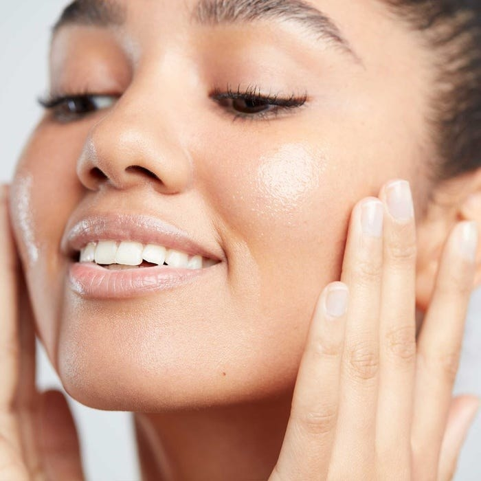 Person rubbing Superfood Facial Oil on face and cheeks