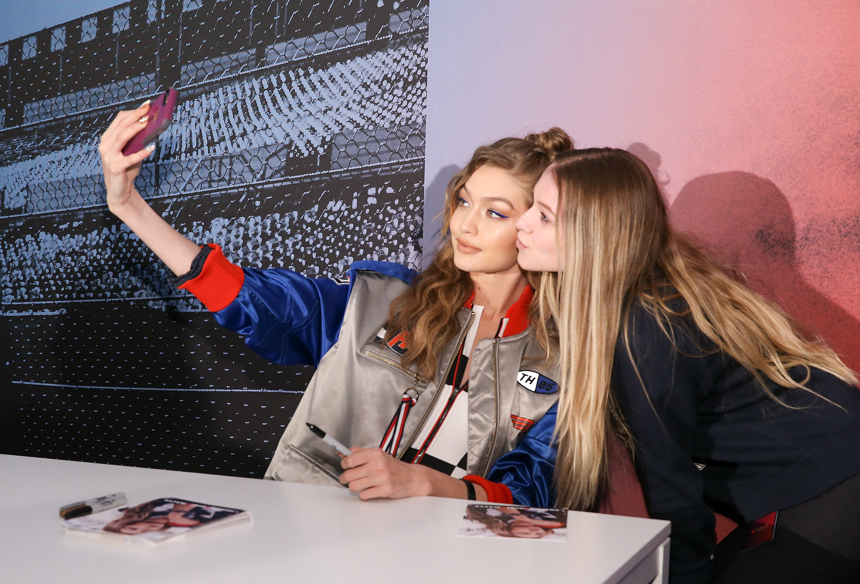 Gigi holds a phone up for a selfie with a fan