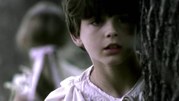 A young Timothée hides behind a tree, while his on-screen sister has her back toward the camera in the background
