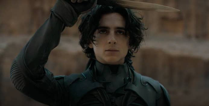 """Timothée as Paul in """"Dune,"""" he holds a sword over his forehead perpendicular to his body"""