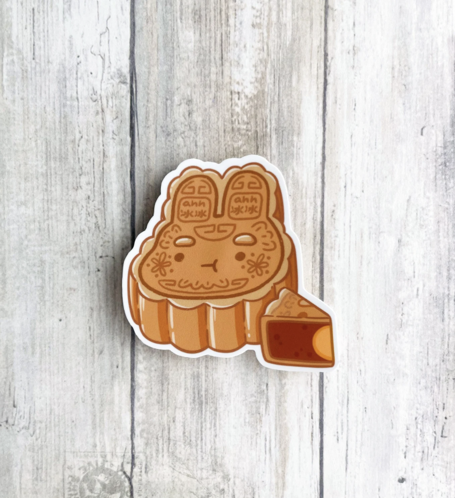 Bunny shaped mooncake sticker with slice of another mooncake next to it.