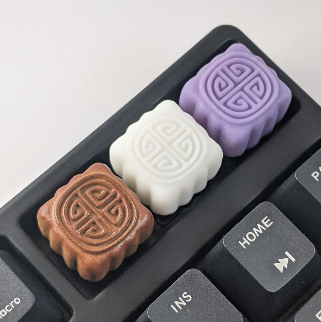 Brown, white, and purple mooncake shaped keycaps.