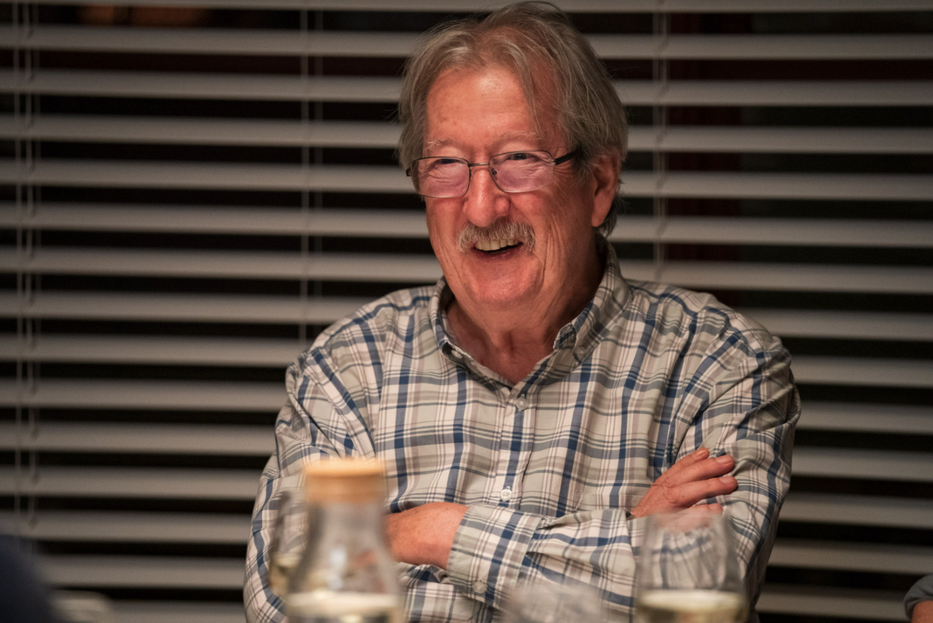 Michael Caton laughing while sitting down at a table