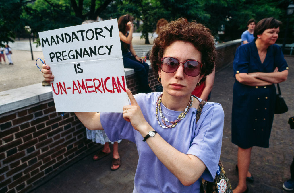 """woman holding sign saying """"mandatory pregnancy is un-american"""""""