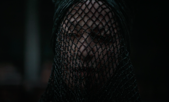 """Charlotte in """"Dune,"""" she wears a black beaded fishnet veil over her face"""