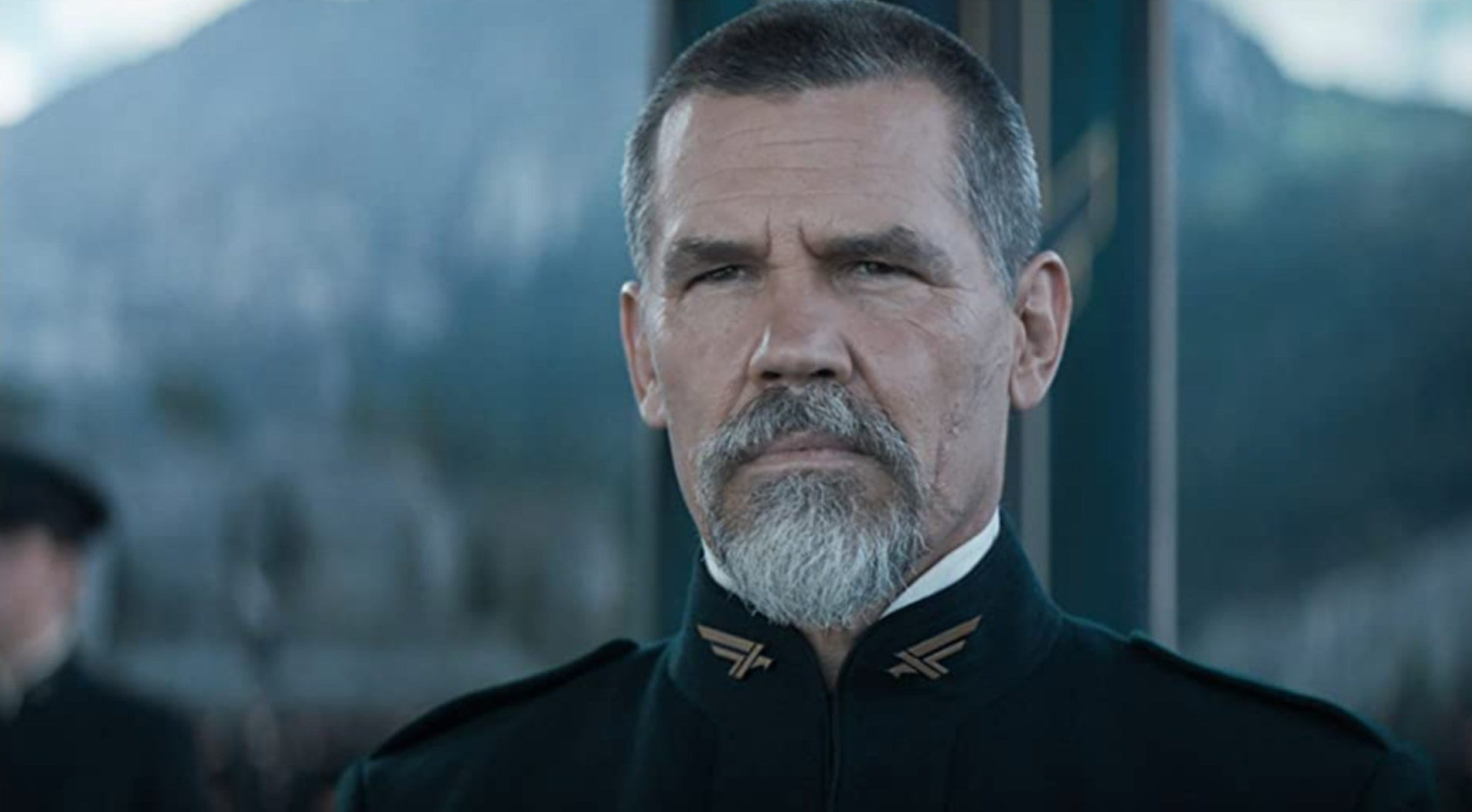 """Josh in a still from """"Dune,"""" he sports a full goatee and black general uniform"""
