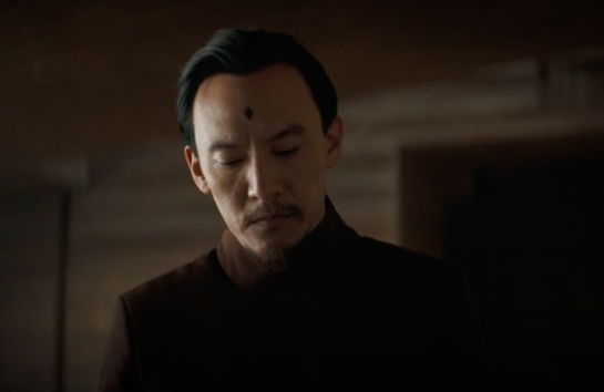 """Chang sports a goatee and brown ensemble in this """"Dune"""" still, he also has a black diamond tattoo on his forehead"""
